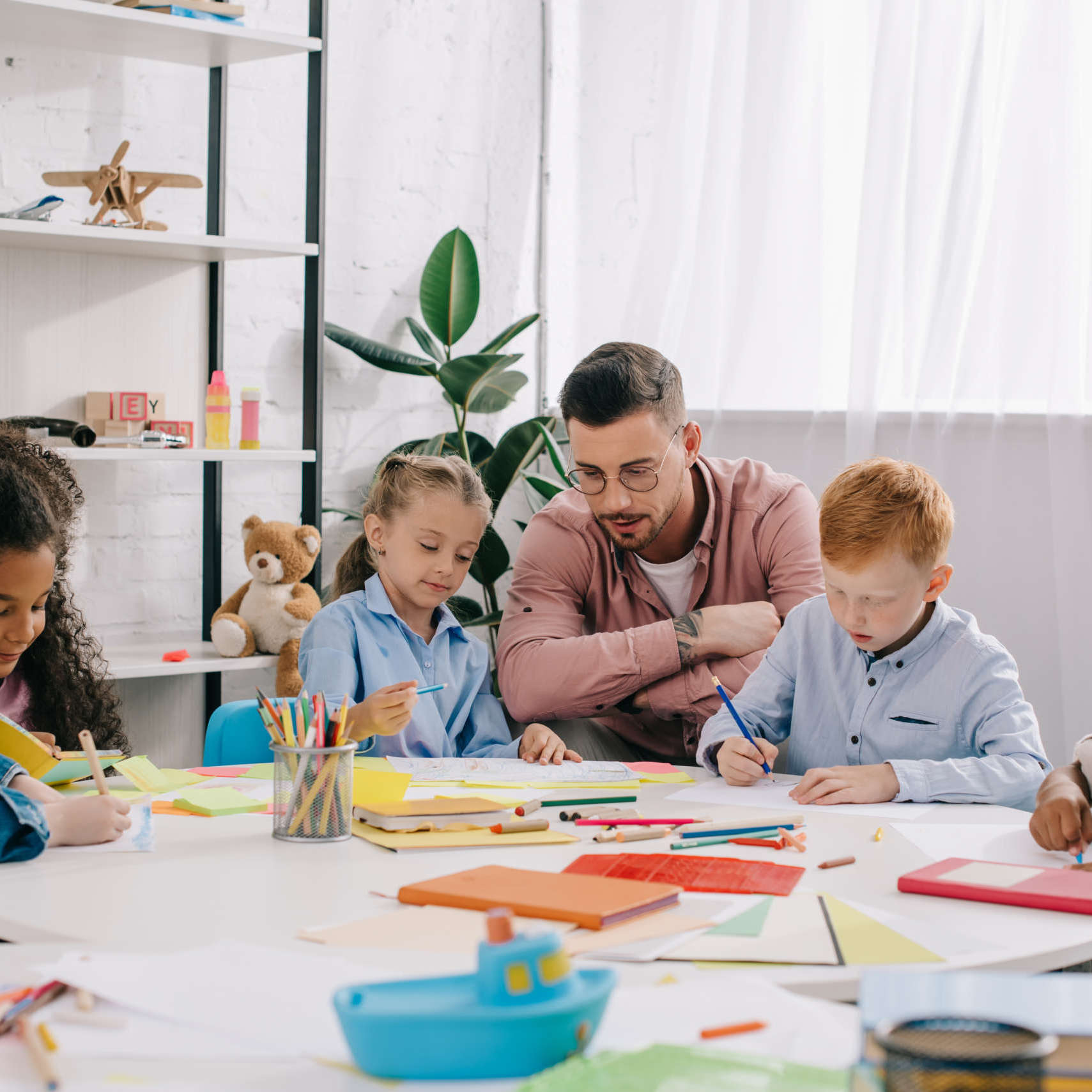 Teacher,And,Interracial,Preschoolers,At,Table,With,Paints,And,Papers