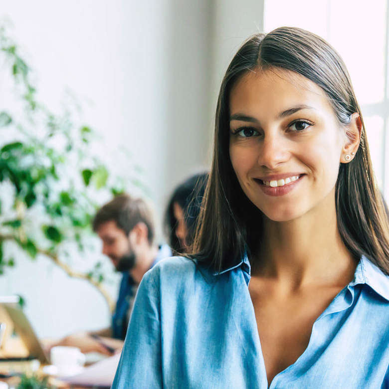 Attractive confident modern business woman in casual clothes looks at the camera with her arms crossed. Modern start-up business team.